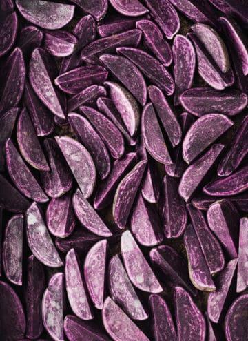 Raw purple potatoes cut into wedges on a baking sheet; overhead shot.