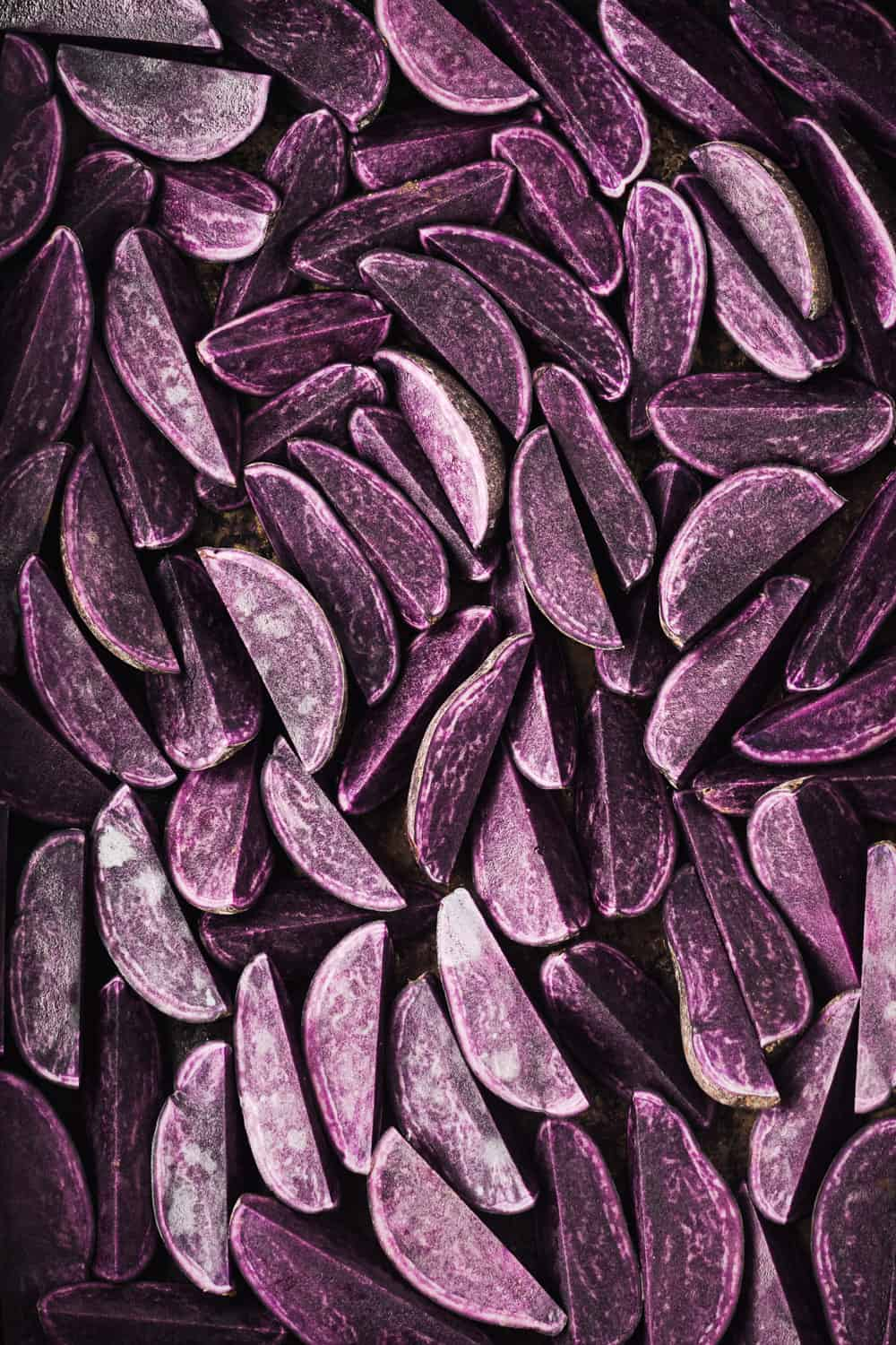 Raw purple potatoes cut into wedges on a baking sheet; overhead shot.