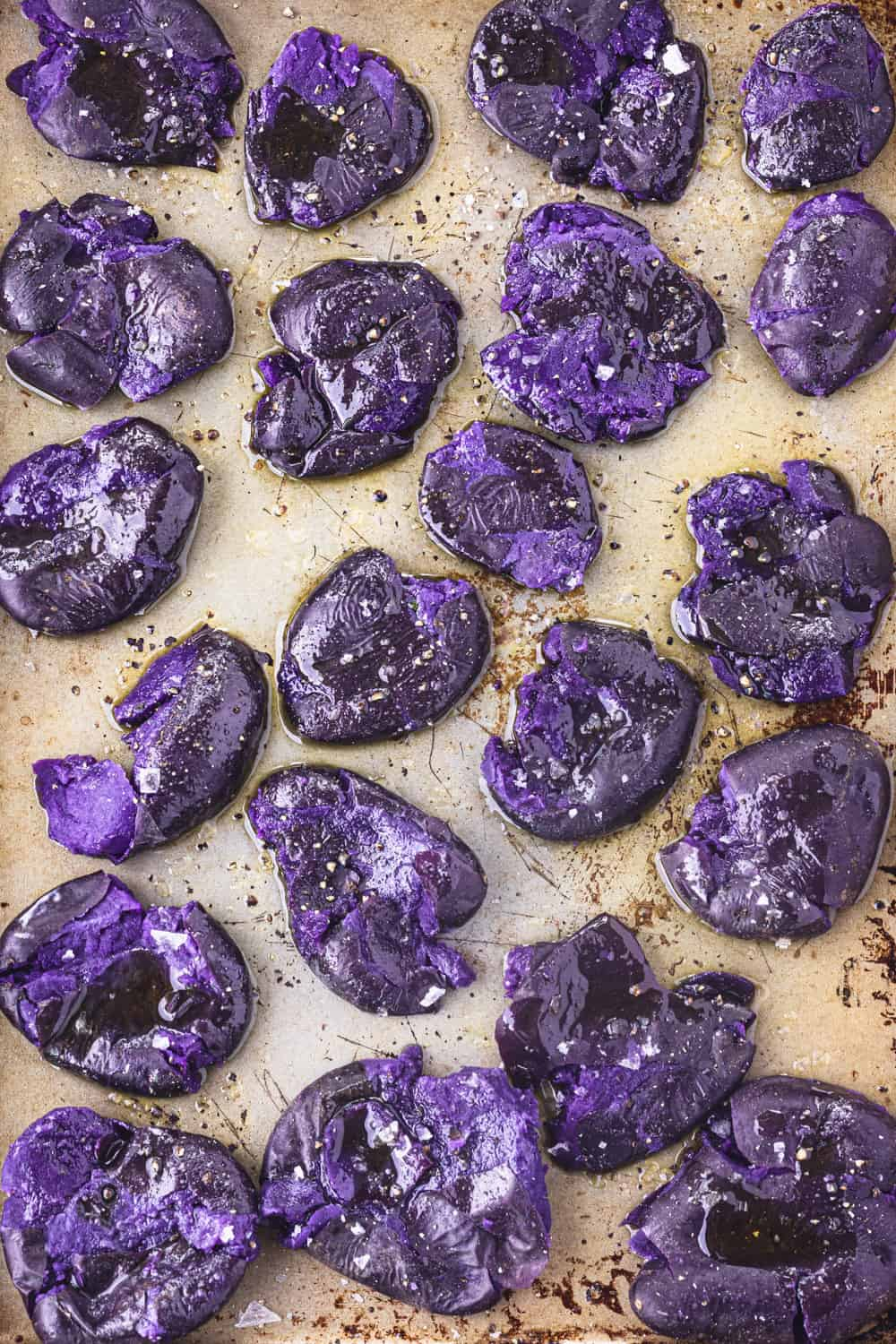 Par-boiled purple potatoes smashed on a gold(ish) baking sheet; sprinkled with flaky salt and overhead shot.