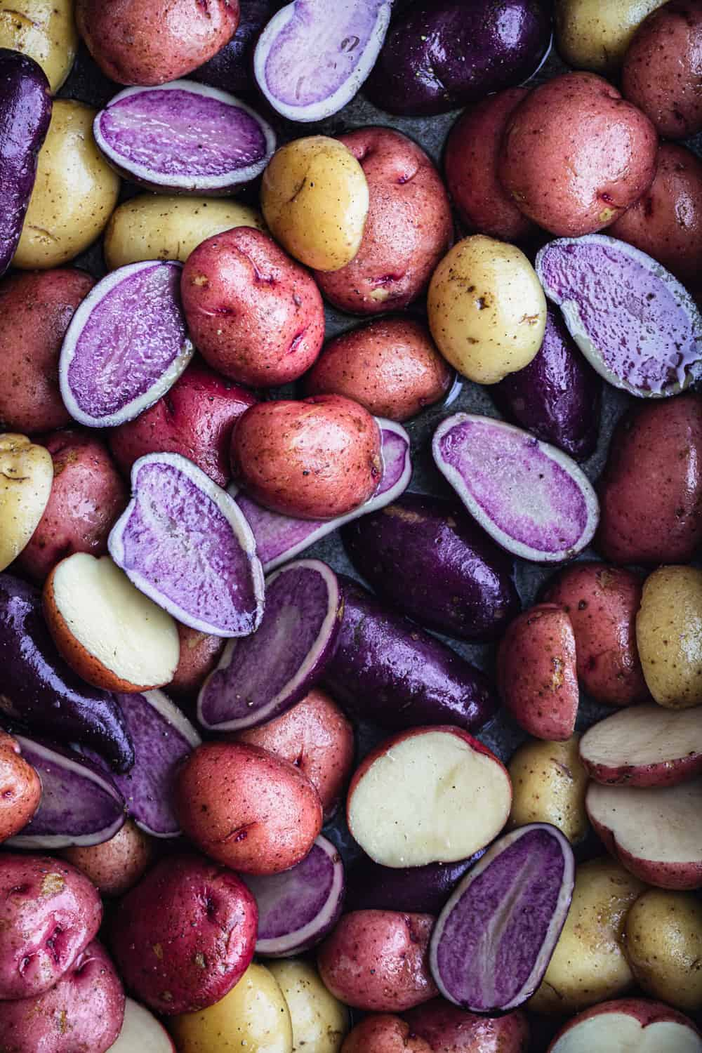 Purple, red and white new potatoes cut in half; on a baking sheet, overhead shot.