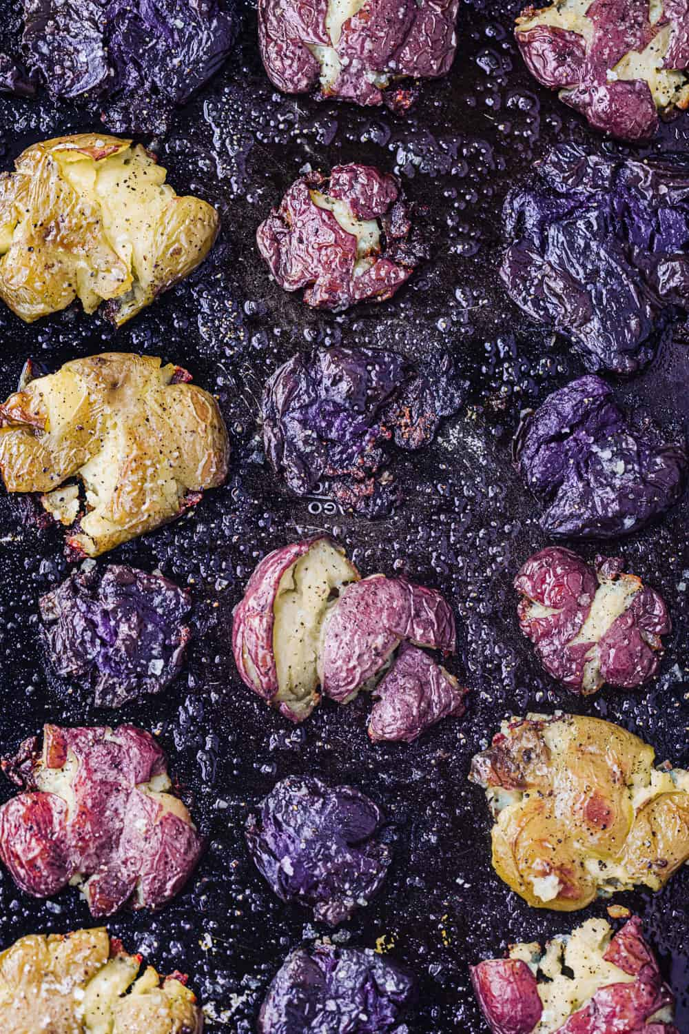 In process shot of roasting smashed purple, red and white potatoes; on a black baking sheet halfway thru cooking; overhead shot.