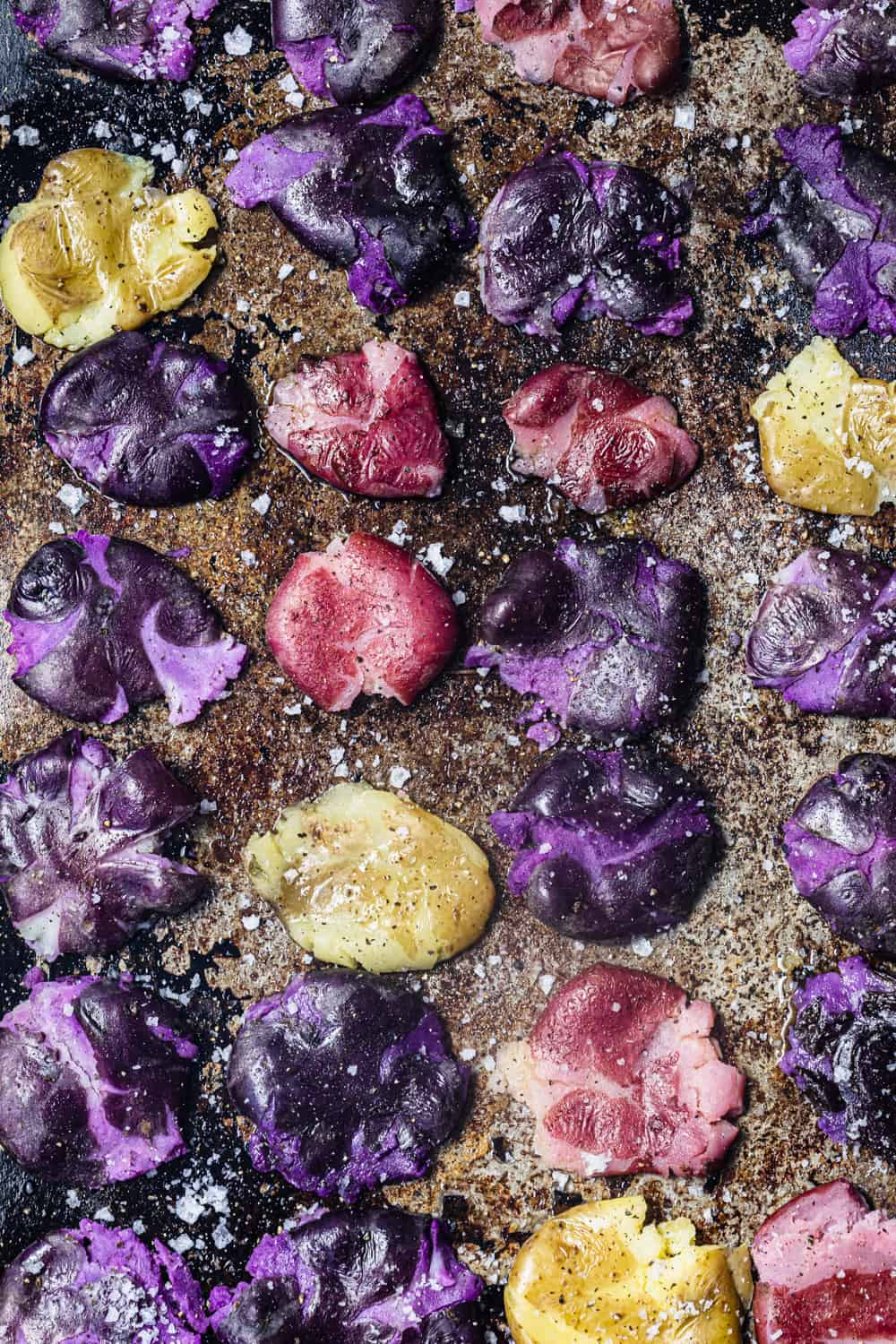 Smashed purple, pink and white potatoes on a baking sheet; pre-oven & overhead shot.
