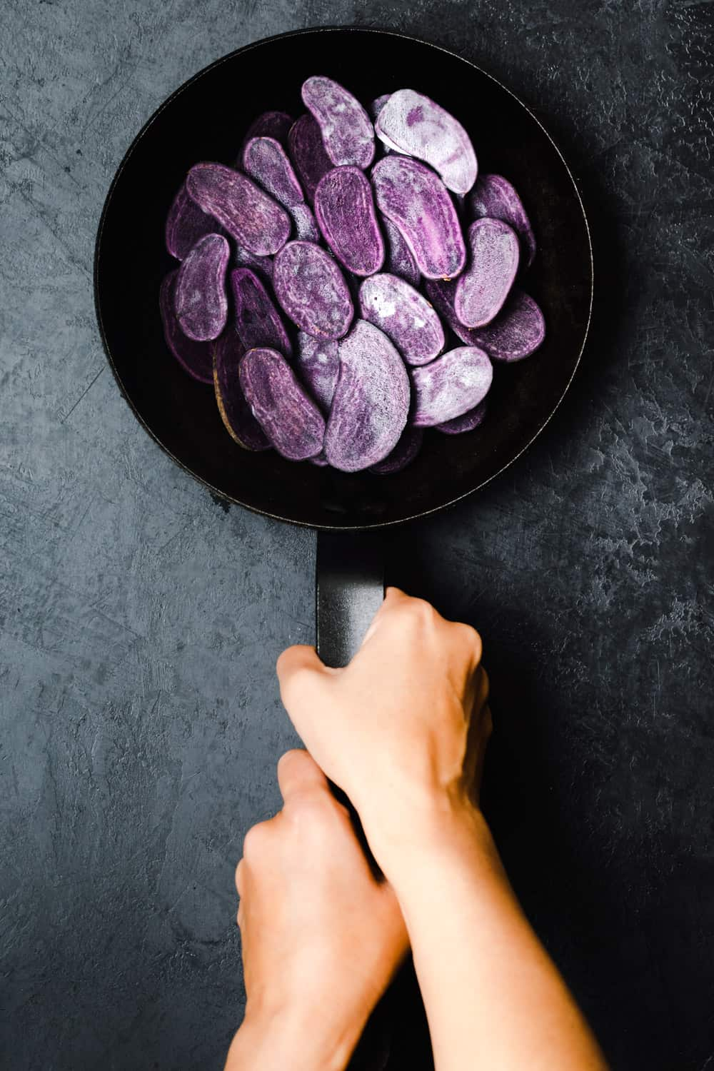 Daniela Gerson holding a cast iron skillet with purple potatoes cut in half on a black background; overhead shot.