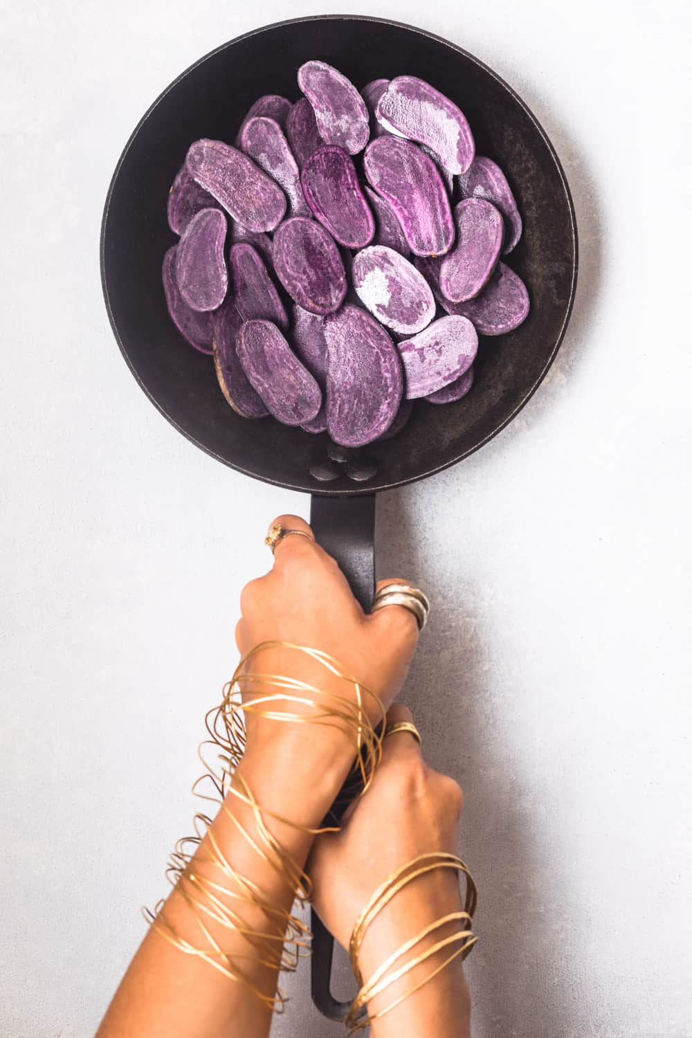 Daniela Gerson holding a cast iron skillet with purple potatoes cut in half on a white background; overhead shot.
