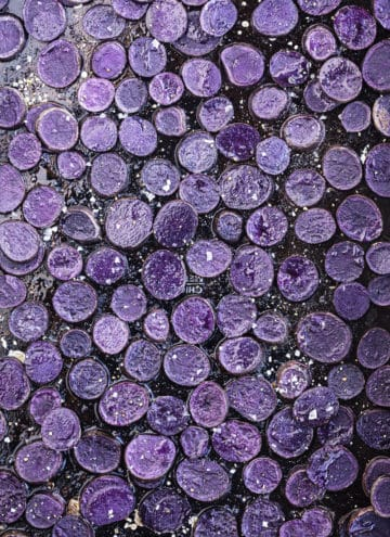 Small purple potatoes cut intro rounds, rounds are on a black baking sheet sprinkled with salt and overhead shot.