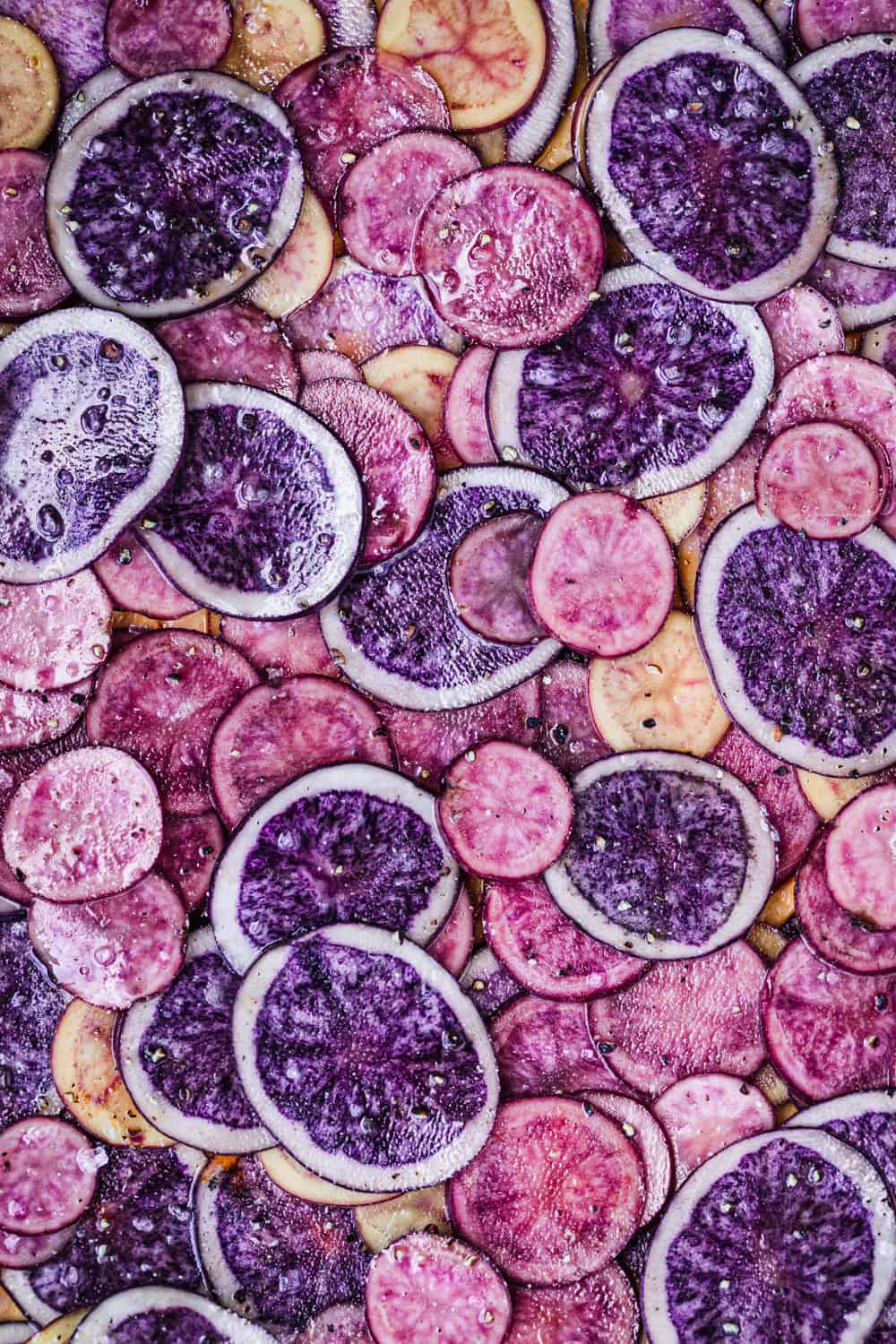 Thinly sliced pink, purple and white potato rounds; tossed with olive oil, sat and pepper; overhead shot.