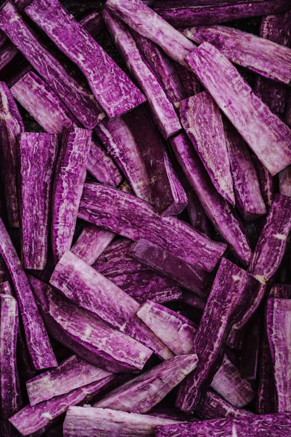 Raw purple sweet potatoes cut into thin wedges, overhead shot.