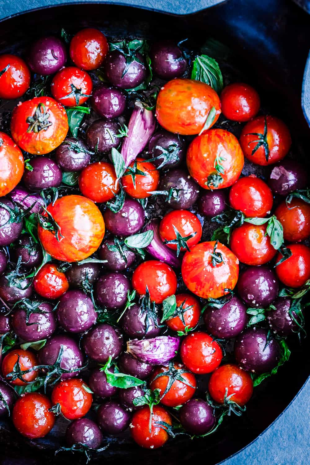 Different shades of red and purple cherry tomatoes in a pan with garlic and basil, overhead shot.
