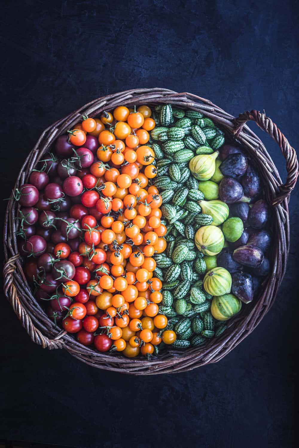 A tomato, cucuamelon and fig rainbow! The tomatoes are on the red-orange-yellow spectrum and the figs and cucamelons are green and purple.