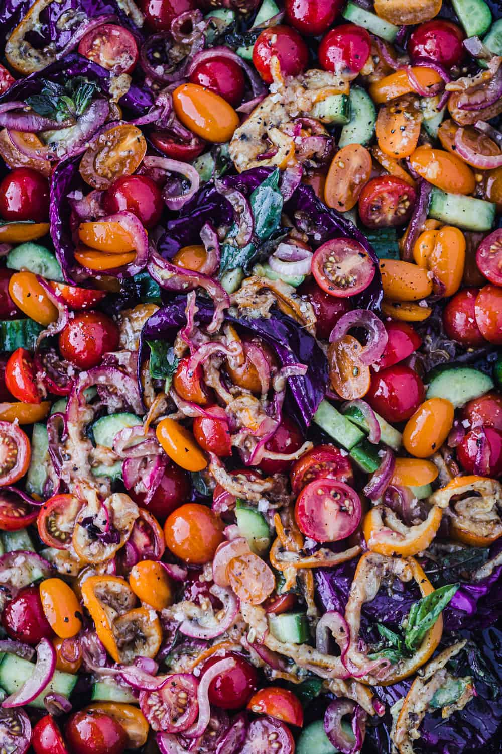 Red, orange and yellow cherry tomato salad, with lemon, purple cabbage and onion; overhead shot.
