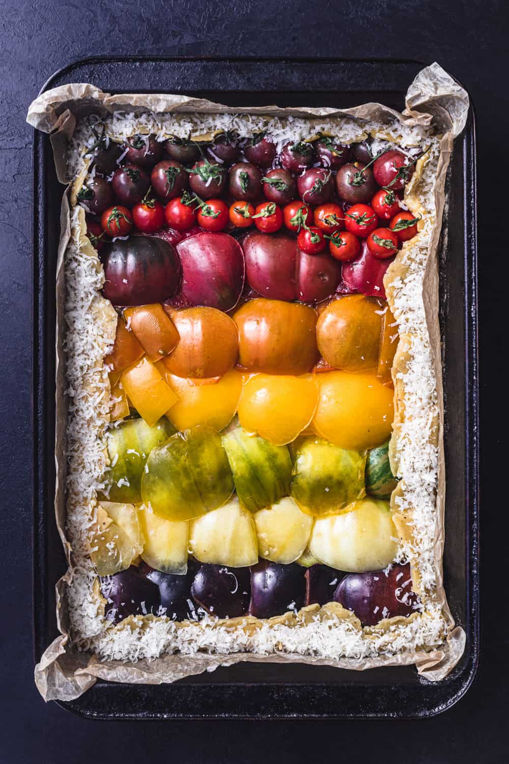 A rainbow heirloom tomato tart, overhead and pre-oven shot. The tomatoes are arranged on the dough like a rainbow, from red to purple.