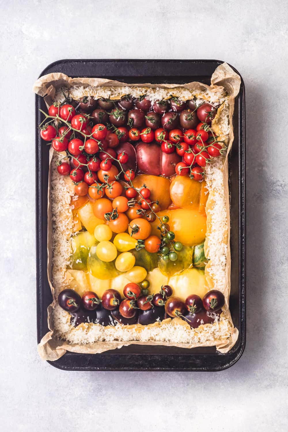 An heirloom rainbow tomato tart! Pre-oven, overhead shot, on a white background.
