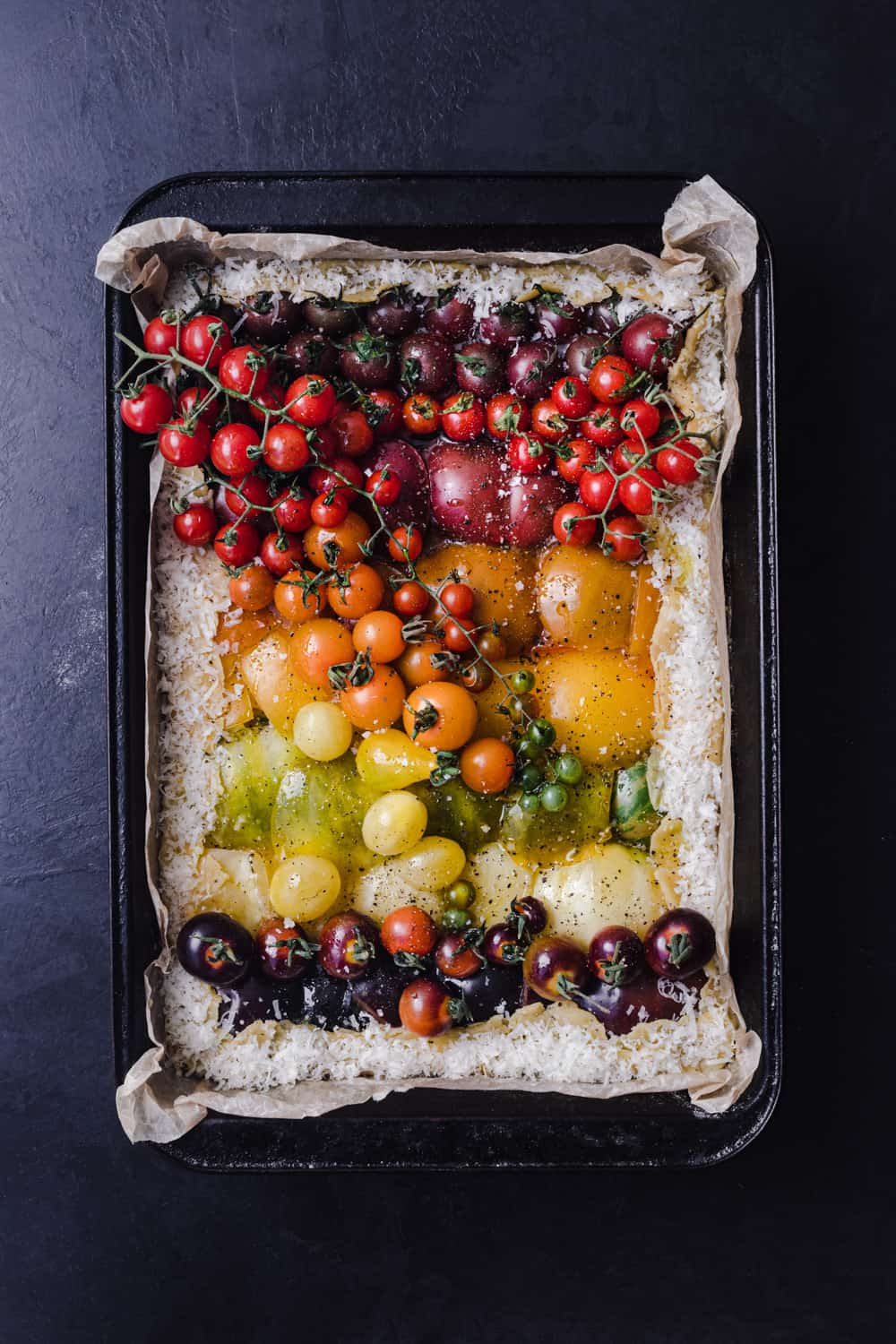 An heirloom rainbow tomato tart filled with very colorful tomatoes! Pre-oven, overhead shot, on a black background.