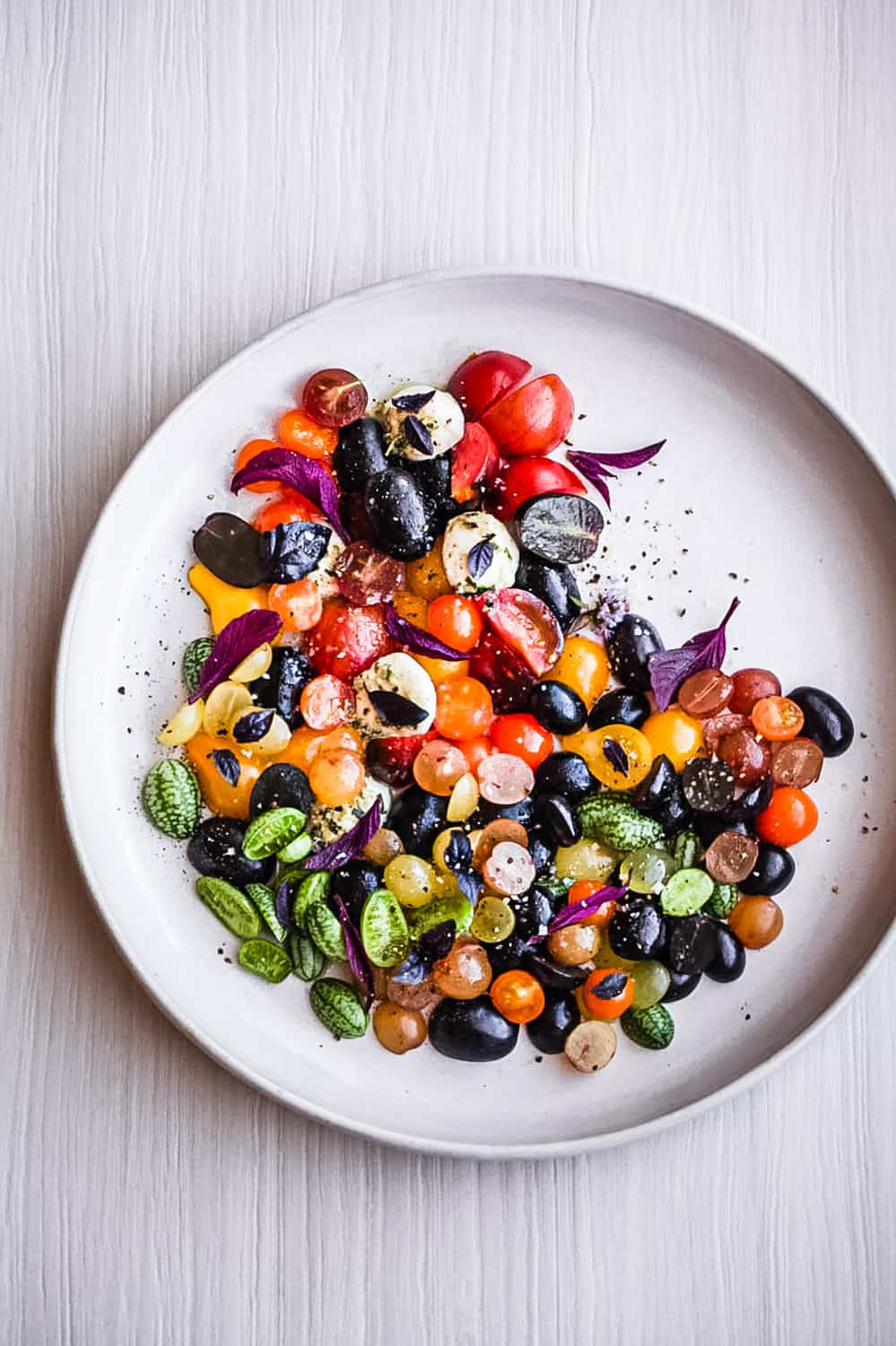 A rainbow tomatoes summer salad on a white plate and white background, overhead shot.
