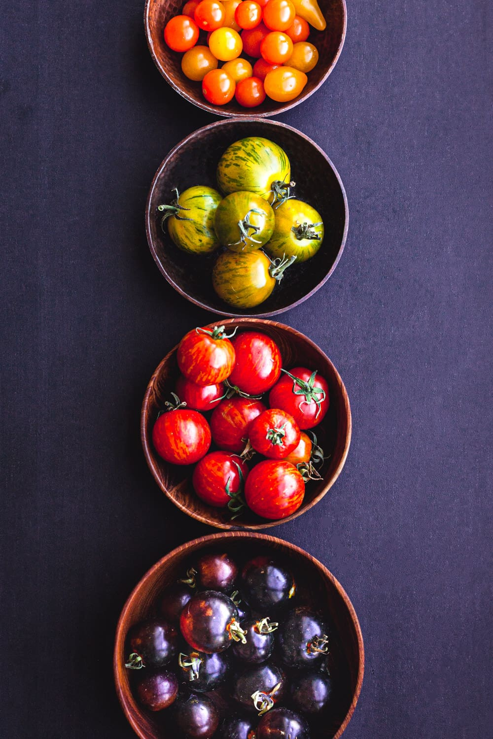 Rainbow tomatoes! There's orange, green stripped, red stripped and red-purple tomatoes, divided into small bowls by color.