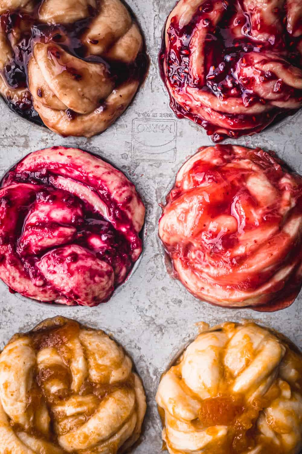 Challah Babka Buns, with all different colors of jam, pre-oven, in a silver muffin tin; overhead shot.