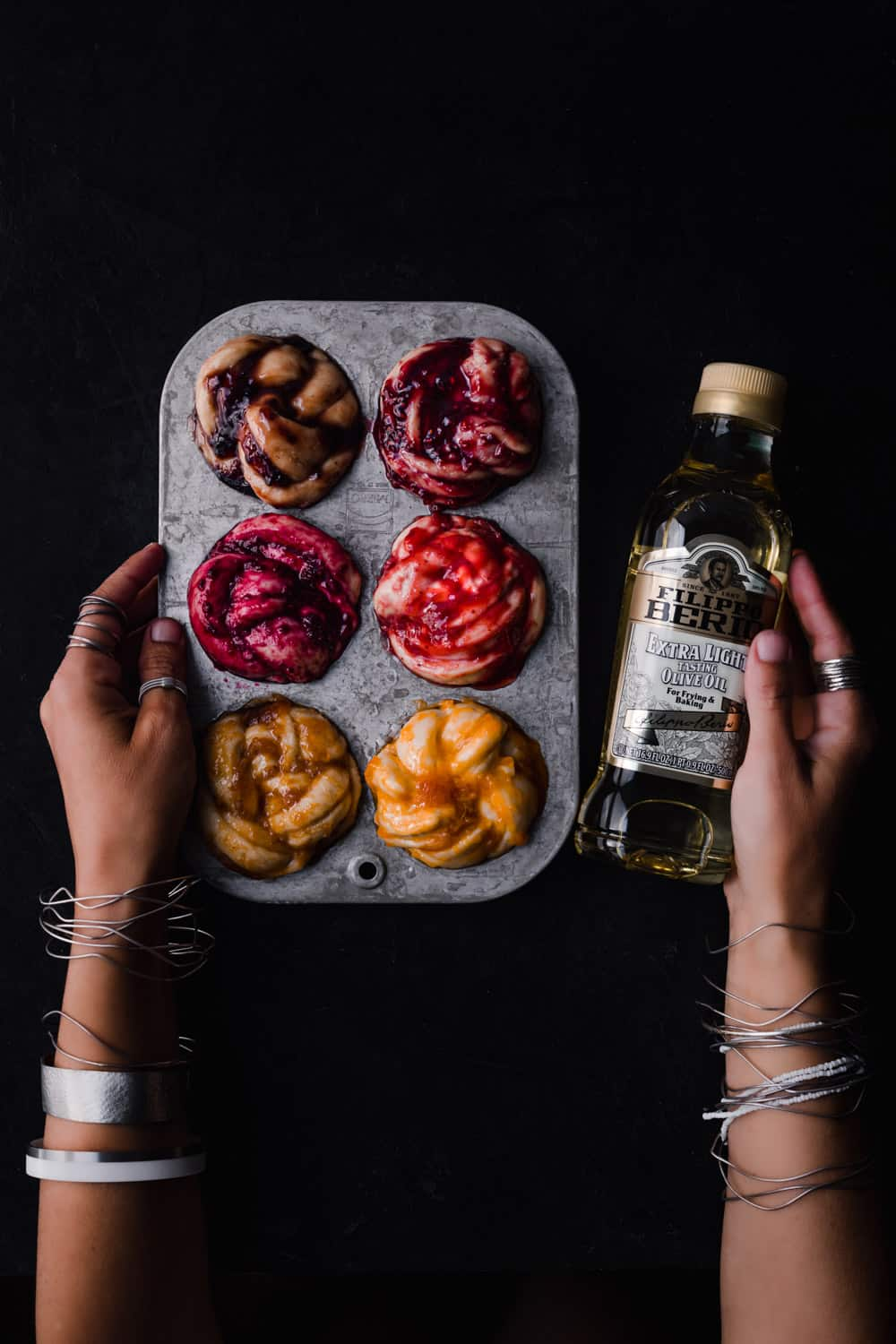 Daniela Gerson holding a bottle of olive oil in one hand and rainbow challah babka buns in a muffin tin in the other on a black background; overhead shot.