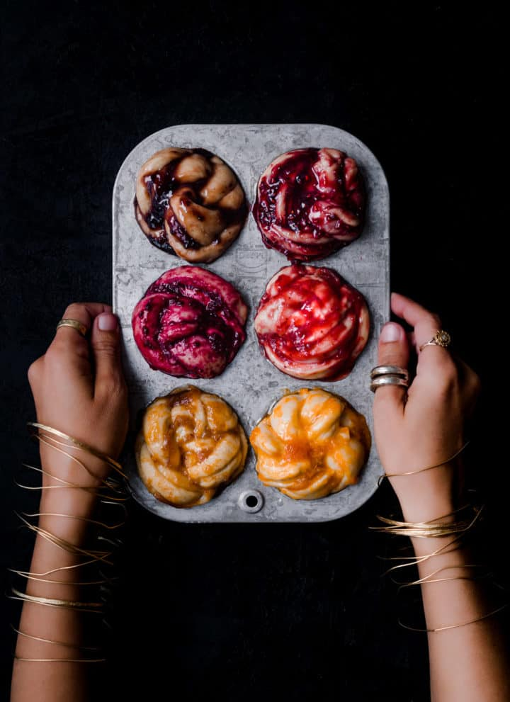Daniela Gerson wearing jewelry and holding a silver muffin tin filled with challah babka buns, all with different color and type of jam; overhead shot.
