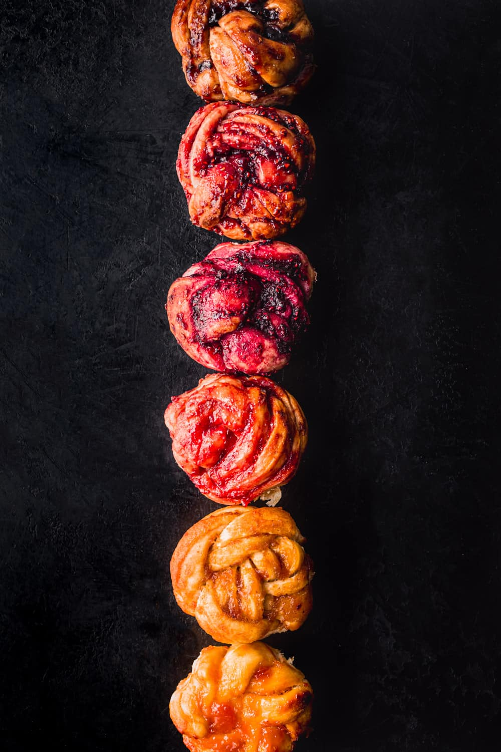 Challah babka buns aligned in a straight line on a black backdrop, all different colors; overhead shot.