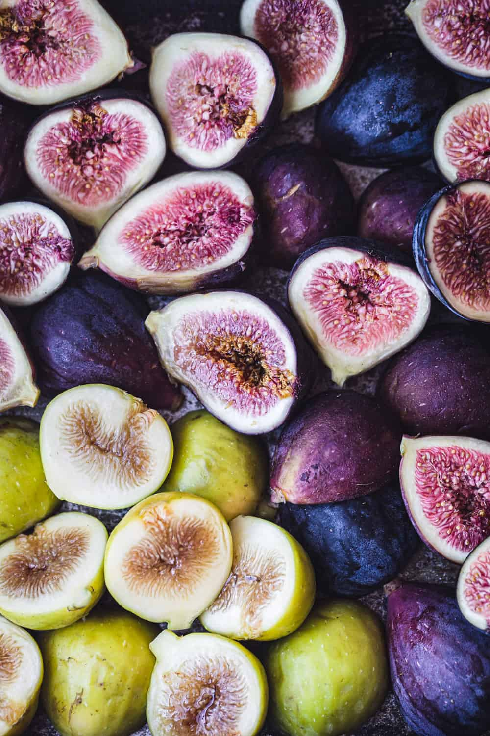 Fresh raw figs, purple and green, cut in half; overhead shot.