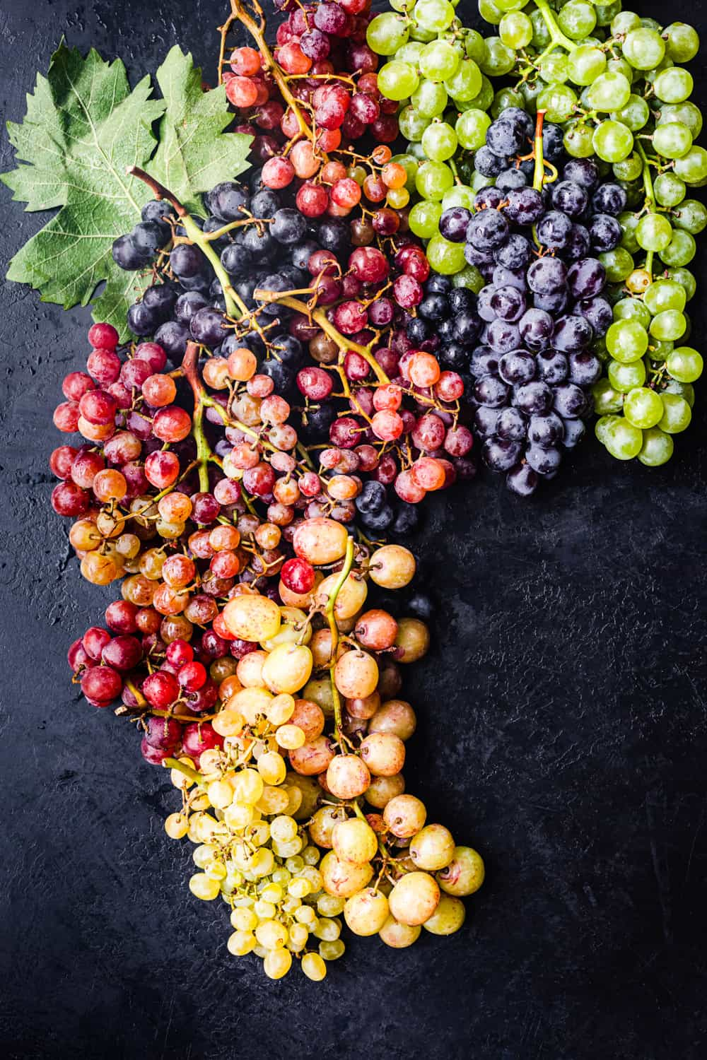 Red, green, orange, yellow, and purple grapes on the vine on a black background; overhead shot.