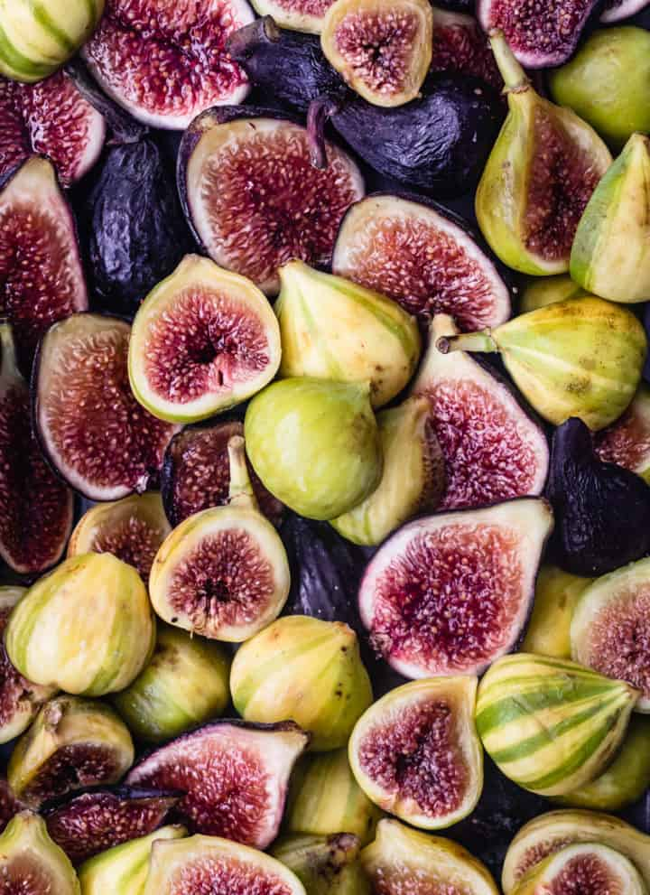 3 varieties of fresh figs, purple and green, cut in half, some are cut side up and some are cut side down; overhead shot.