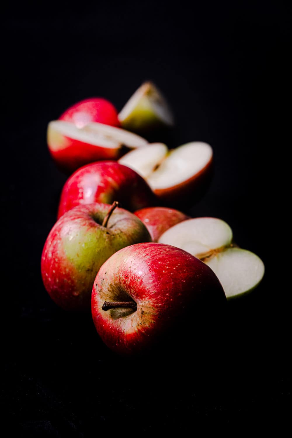 Little red apples, side angle shot, whole, cut in half and quartered; on a black background.