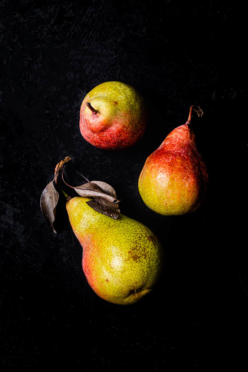 3 green and red pears shot lying down and standing up on a black background; overhead shot.