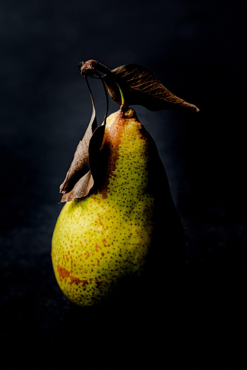 One side of a pear that's green, with the leaves still on it, straight on and up close shot, on a black background.