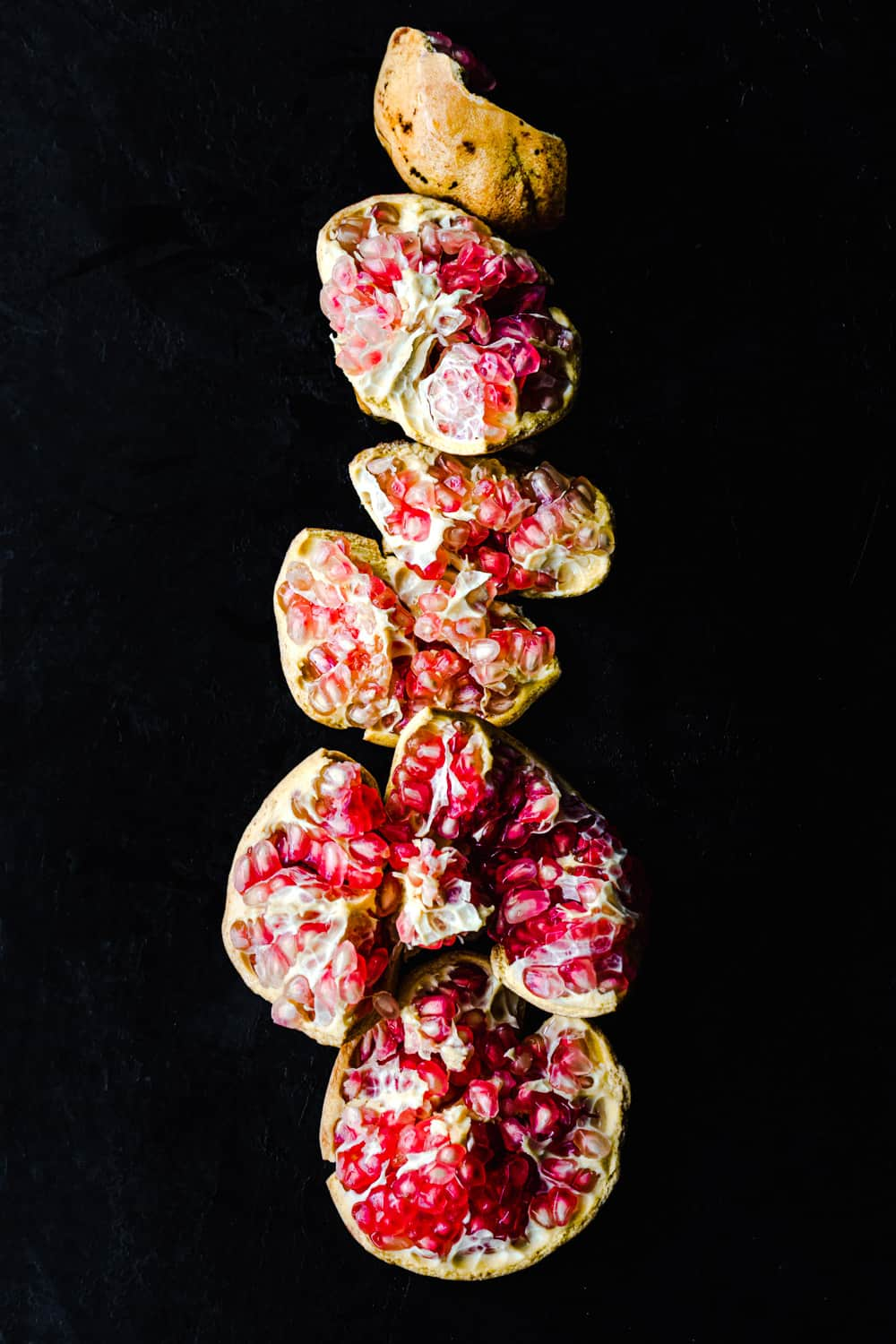 A white pomegranate with pink arils! Cut until pieces and arranged in a vertical l one, cut side up; overhead shot on a black background.