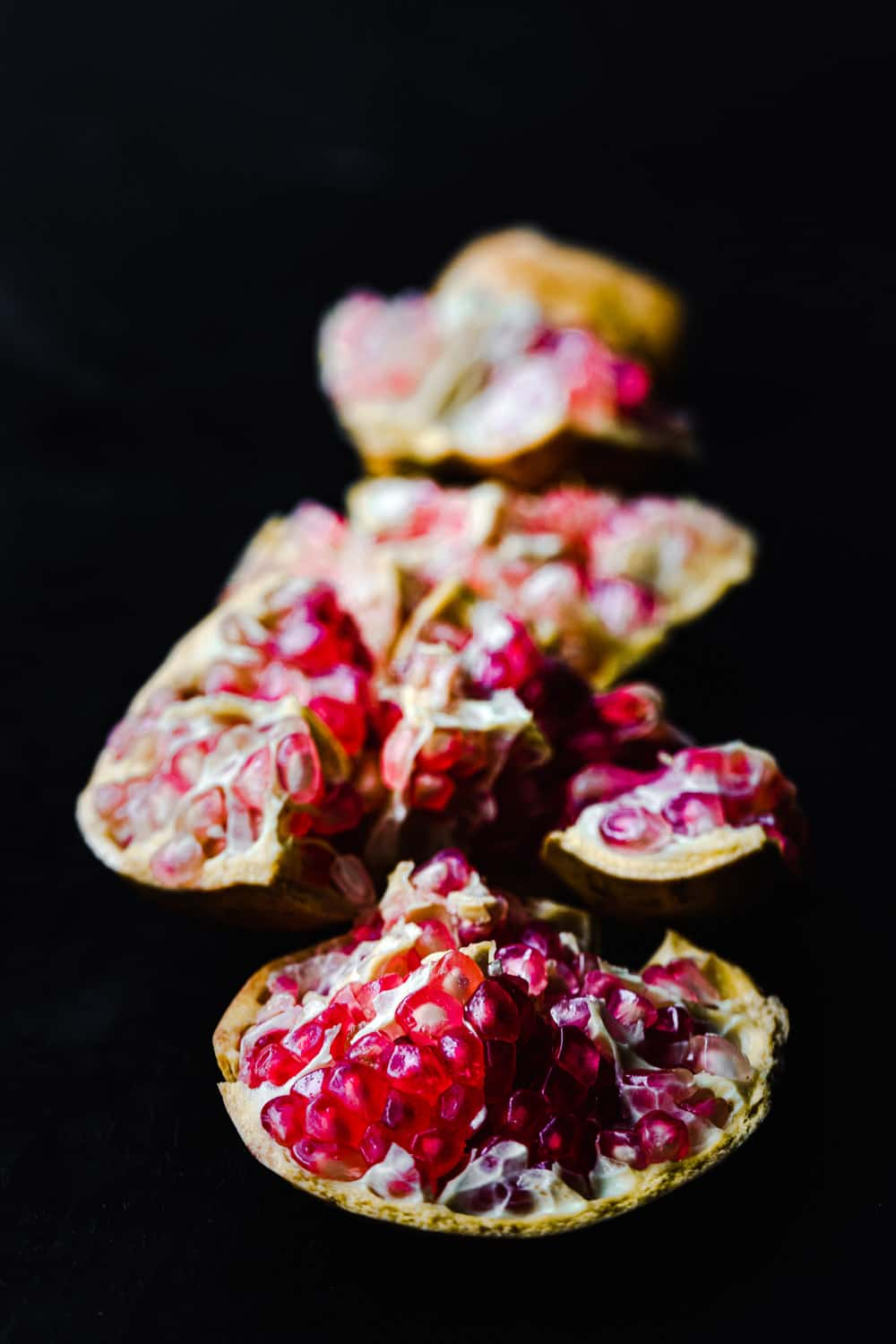 Side angle shot of a white pomegranate cut into pieces with the pink arils exposed, on a black background.