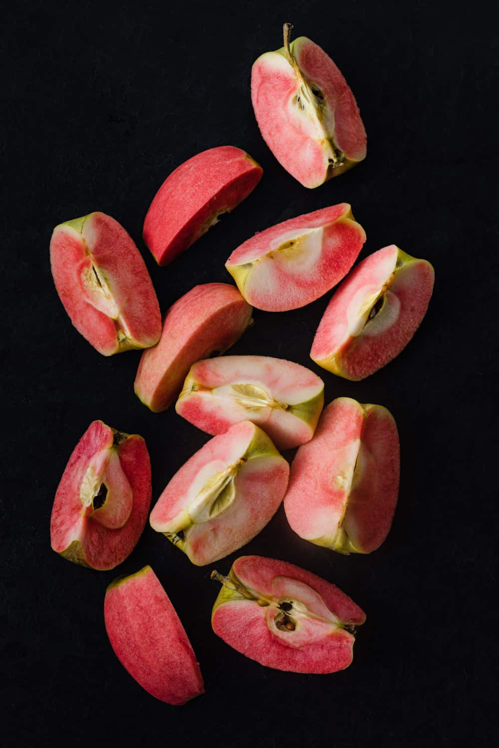 Pink Hidden Rose apples, cut into quarters, on a black background; overhead shot.
