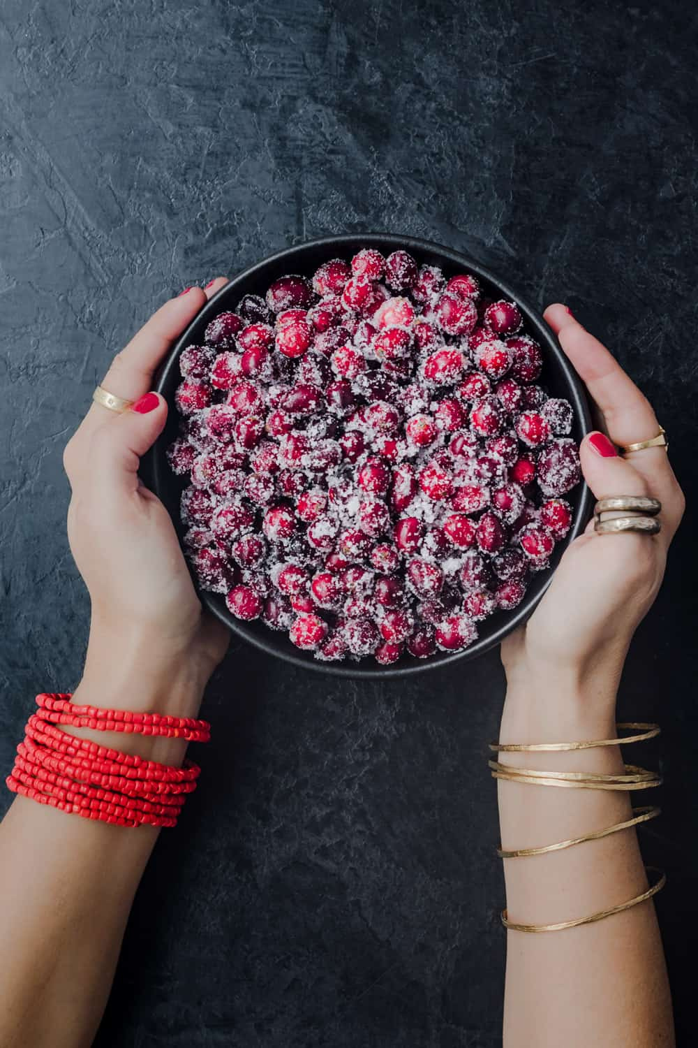 Daniela Gerson holding a bowl of black sugared cranberries; overhead shot.