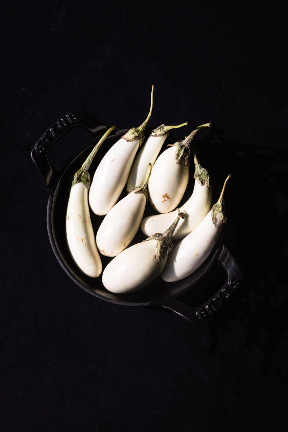 Little white eggplants, that are fresh and whole, in a black bowl on a black background; overhead shot.
