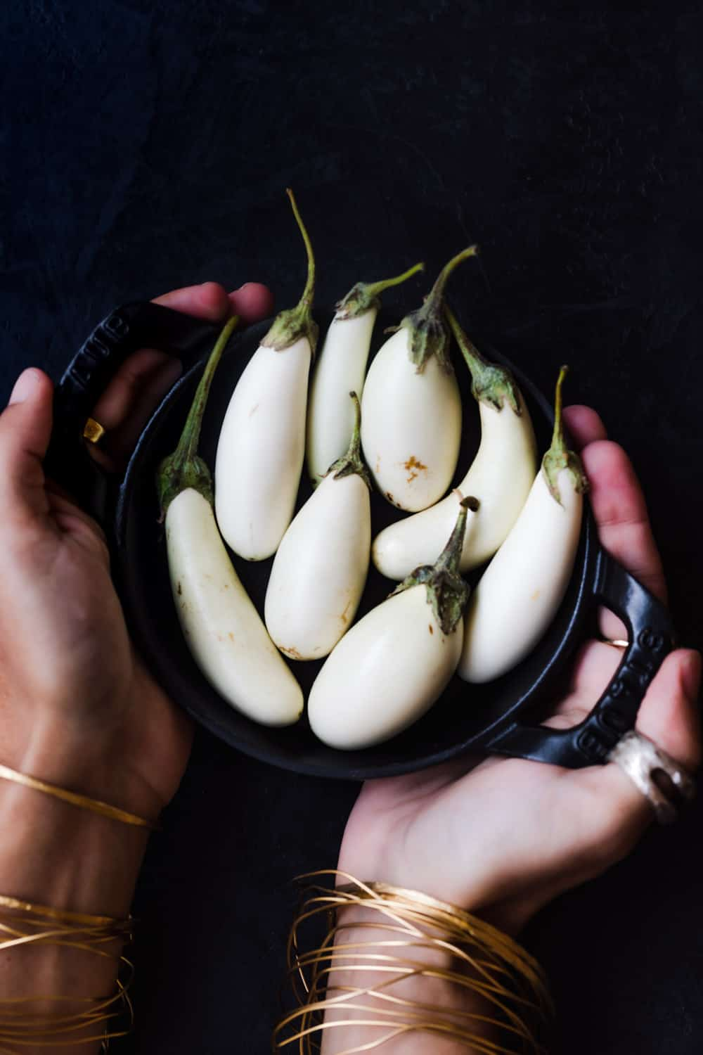 Daniela Gerson carrying a little black bowl filled with little white eggplants, on a black background.