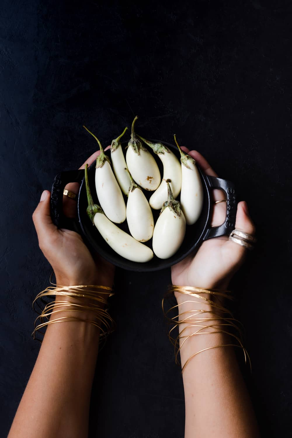 Black bowl filled with white eggplants; carried by Daniela Gerson wearing gold rings and bracelets on a black background.