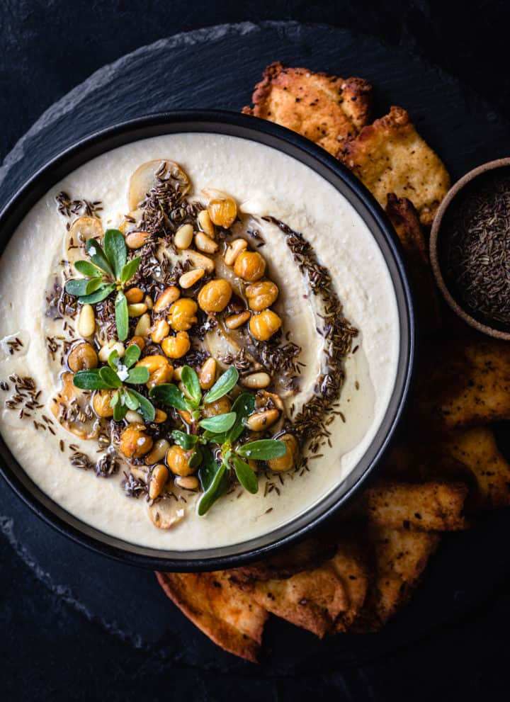 Hummus with tahini topped with cumin seed oil, garlic, crispy garbanzo beans, and fresh herbs; served with crispy pita chips; overhead shot.