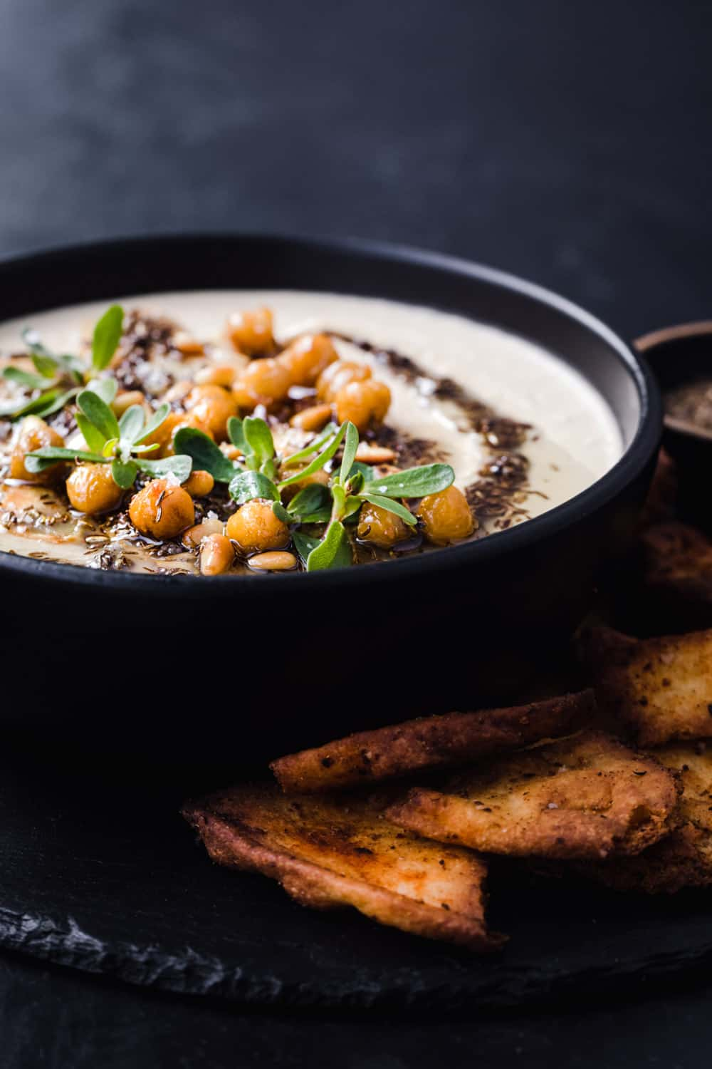 Side angle shot of finished hummus with tahini in a black bowl, served with crispy pita chips on a black slate.