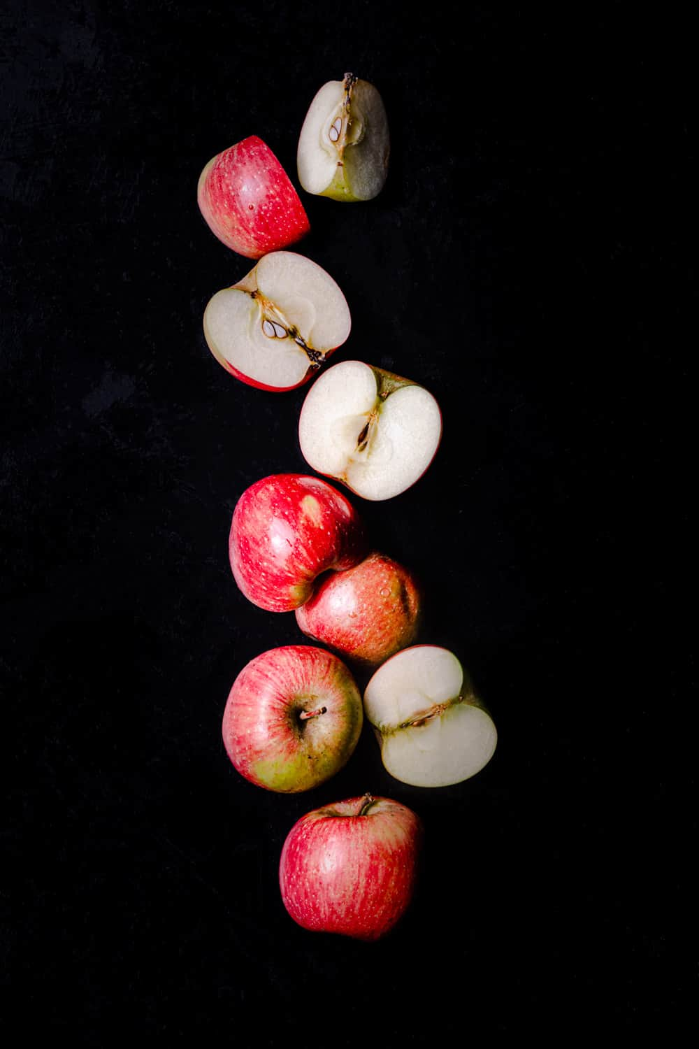 Little red apples, whole, cut in half and quartered, on a black background; ; overhead shot.