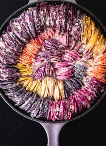 Rainbow root veggies including carrots, beets, potatoes, sweet potatoes, radishes and parsnips made into a very colorful hasselback gratin; proven shot.