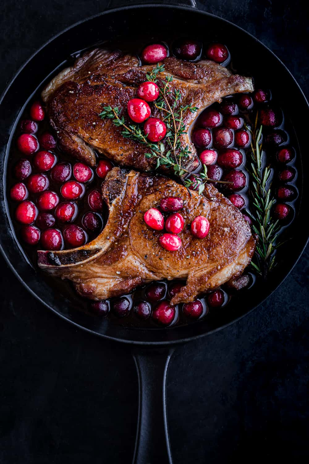 Post sear and pre-oven pork chop overhead shot; chops are in a cast iron skillet with the cranberry sauce on a black background.