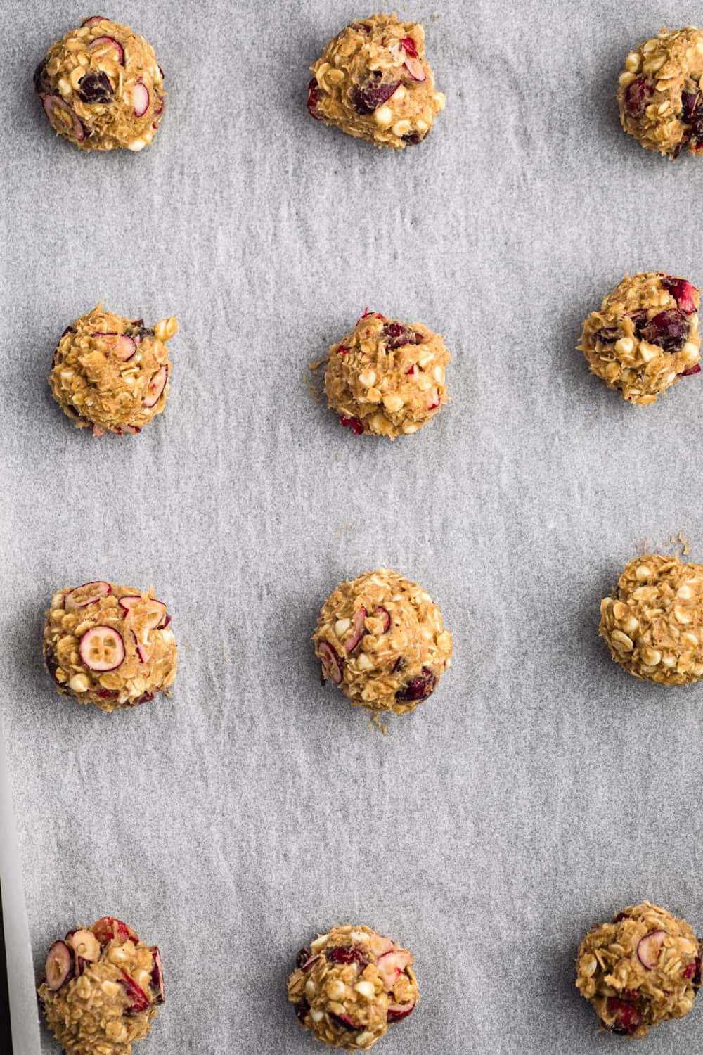 12 raw cranberry white chocolate and oatmeal cookies balls on a sheet pan with parchment paper, all ready to go into oven; overhead shot.