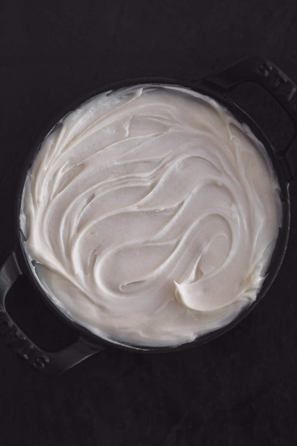 Vanilla mascarpone filling, freshly made, in black bowl with black handles, on a black background; overhead shot.