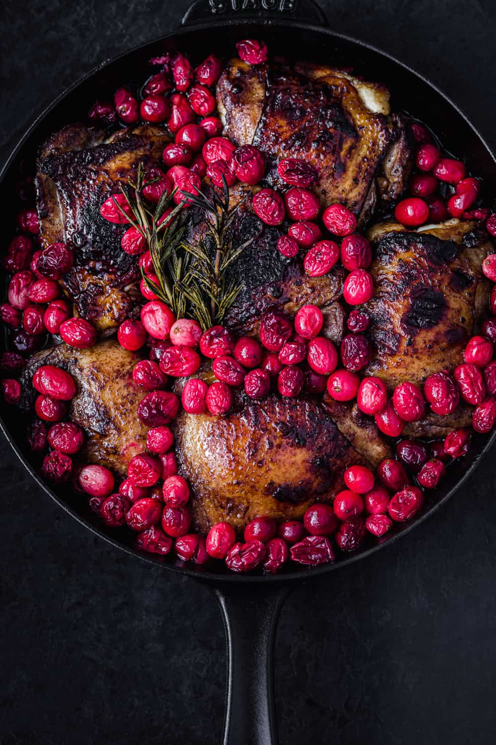 cranberry chicken in a skillet, post oven and all done! Overhead shot on a black background.