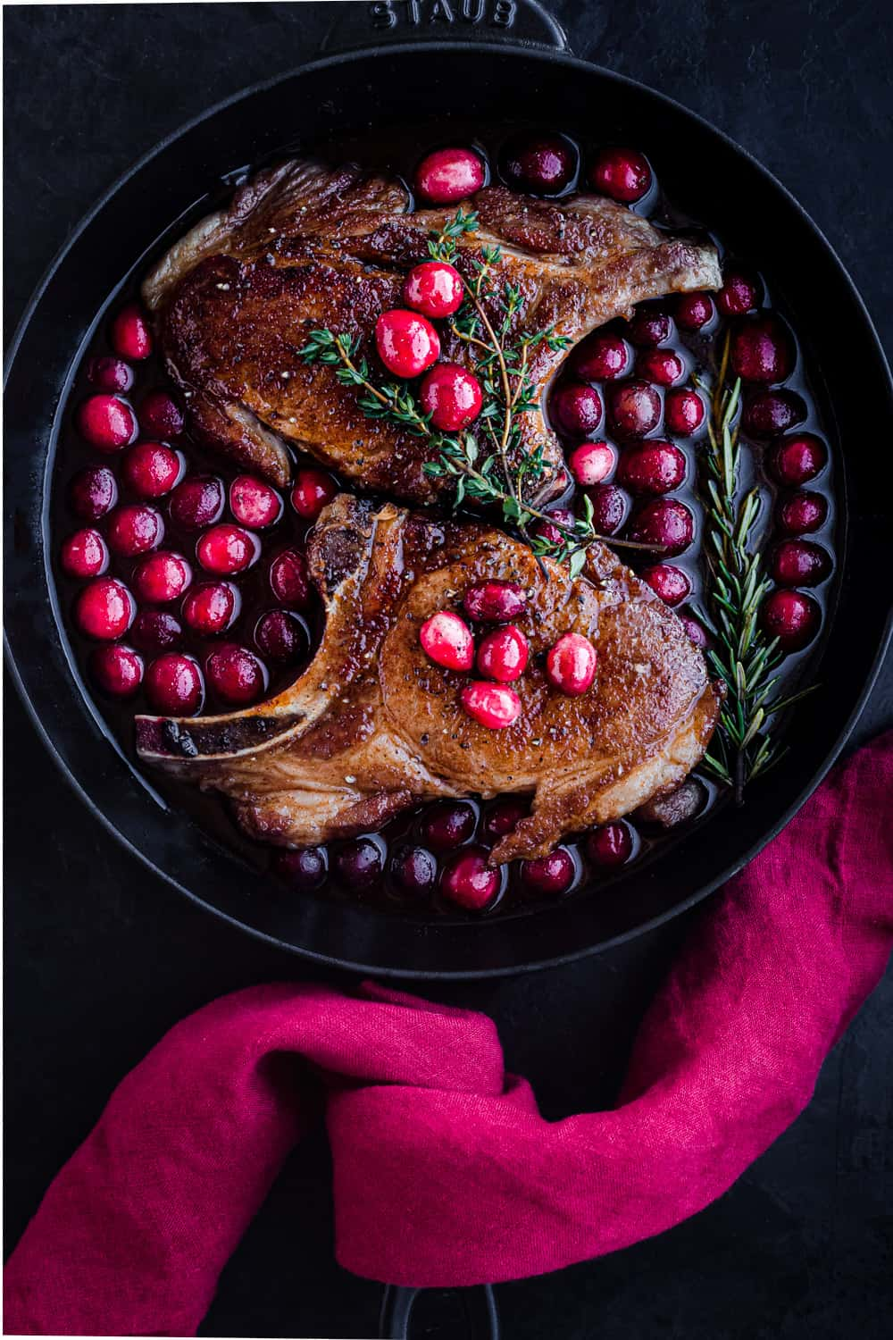 Post sear and pre-oven pork chop overhead shot; chops are with the cranberry sauce in a cast iron skillet with a red linen on the handle; black background.