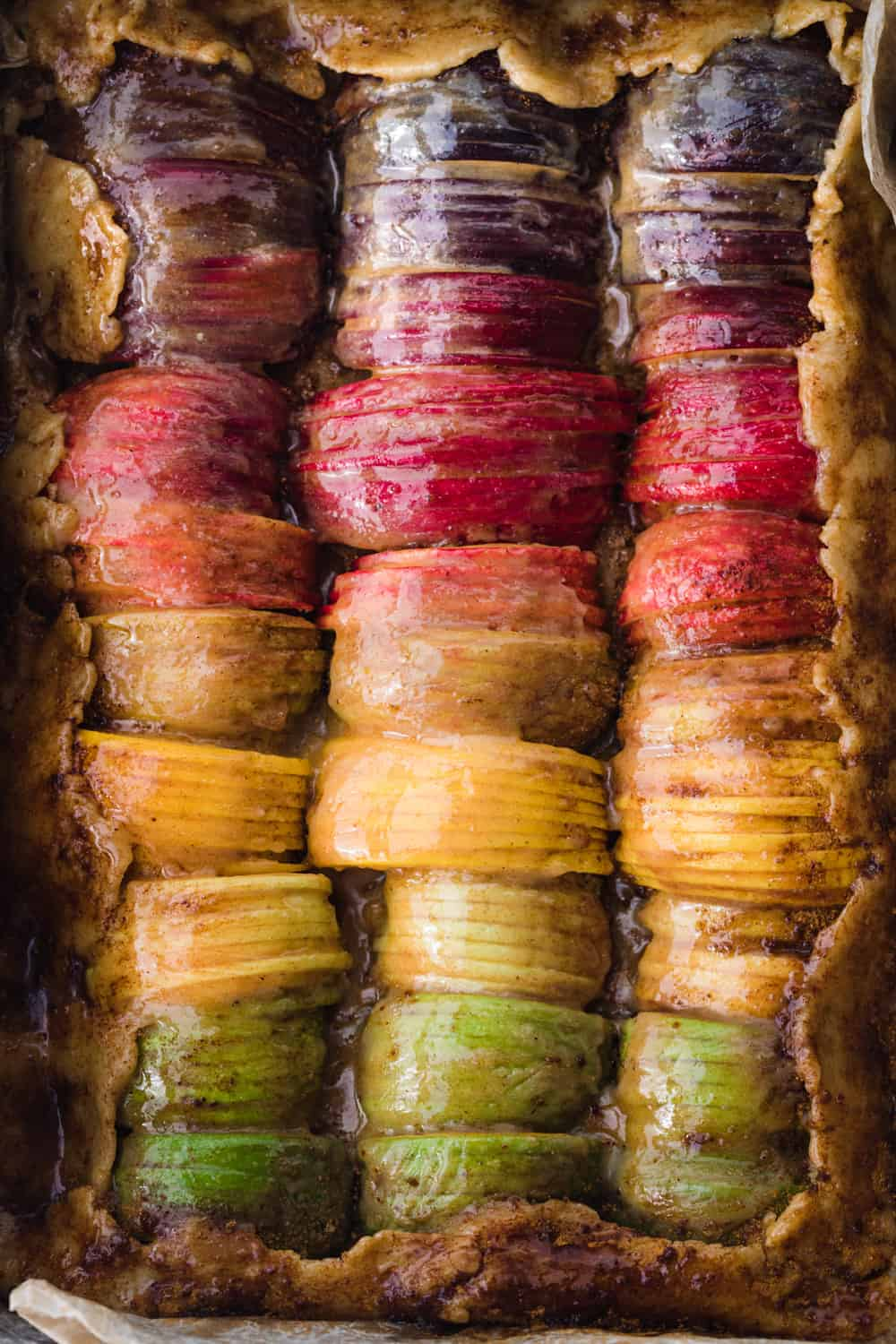 Pre-oven rainbow apple galette shot - apples brushed with butter, sugar and spices; all ready for oven; overhead shot.