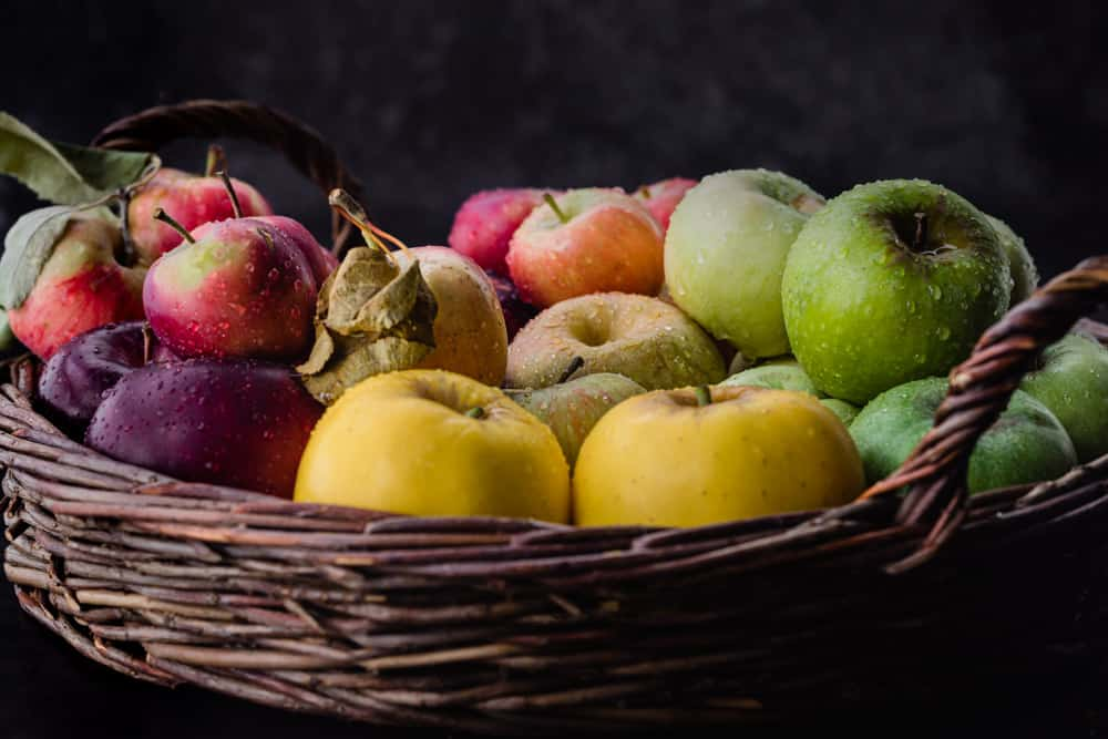 Red, pink, yellow, green and purple apples in a woven basket, side angle shot.