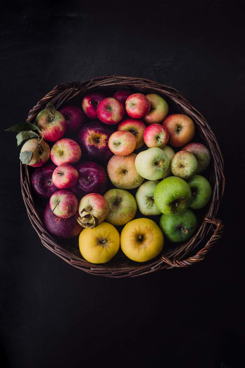 Apples in every color of the rainbow! In a woven basket; overhead shot on a black background.