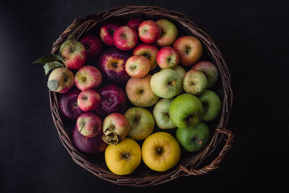 Red, pink, yellow, green and purple apples in a woven basket; overhead shot on a black background.