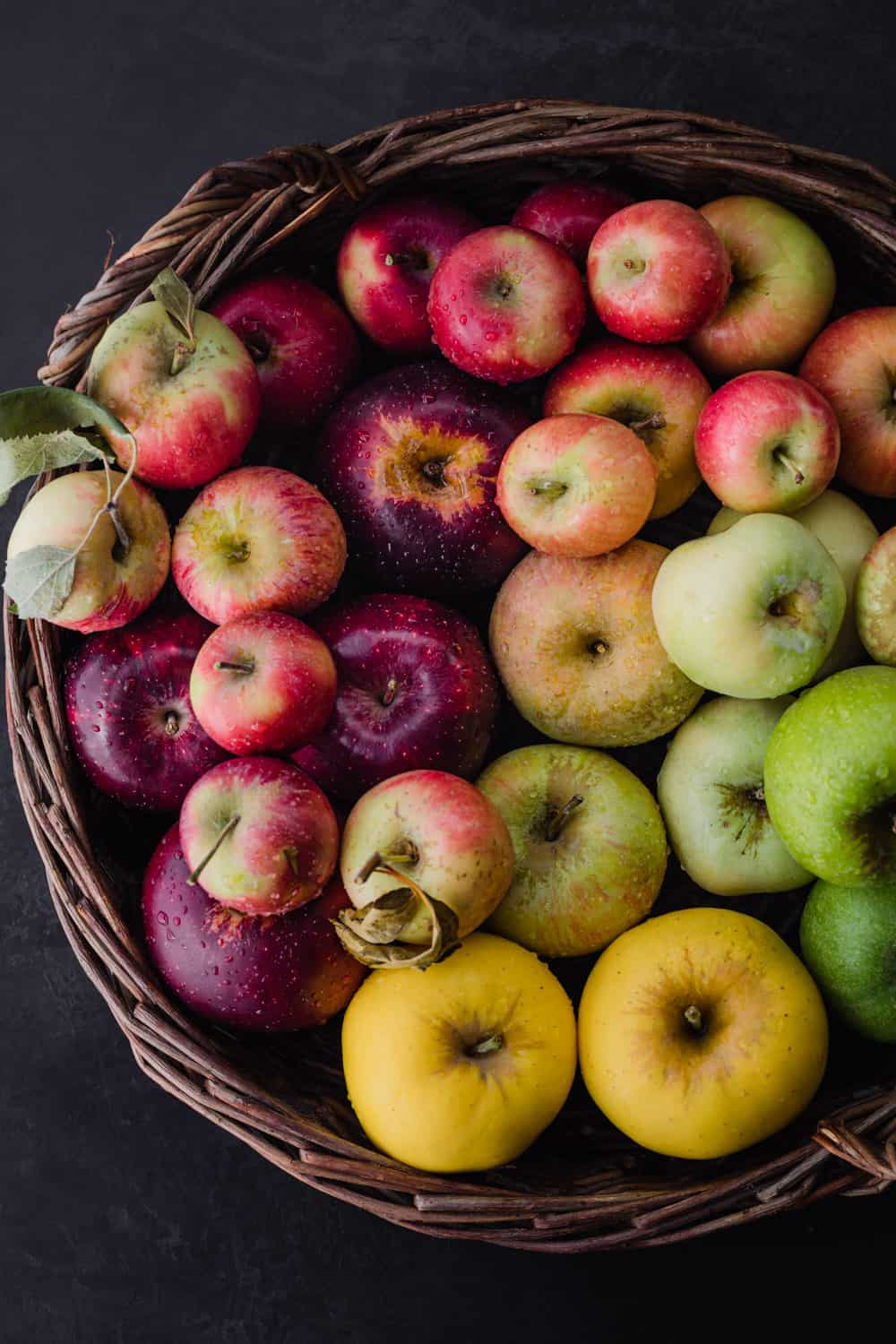 Close up shot of apples in all sorts of different colors; in a woven basket, right side of basket is cut off; overhead shot; black background.